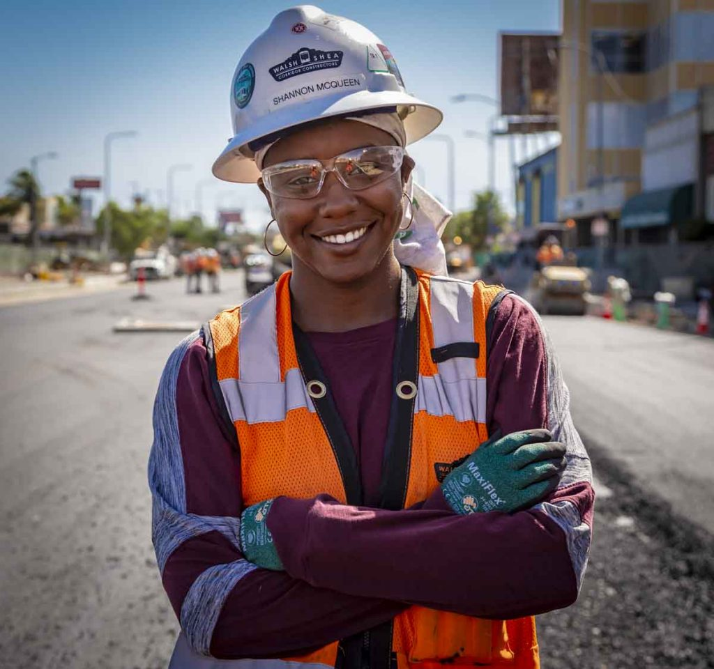 Female construction worker smiling with arms crossed